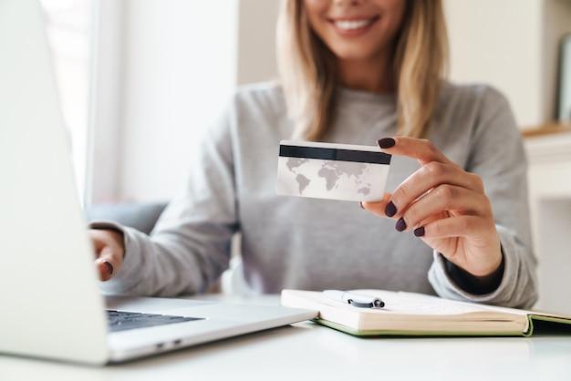Uśmiechnięta kobieta w okularach, korzystająca z laptopa, trzymając kartę kredytową w salonie