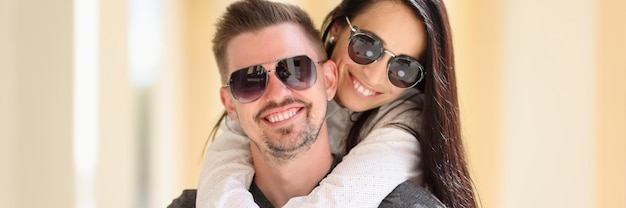 Uśmiechnięta kobieta w okularach przeciwsłonecznych trzyma kawę i przytula mężczyznę