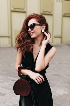 Uśmiechnięta kobieta w okularach przeciwsłonecznych trzyma modną torebkę