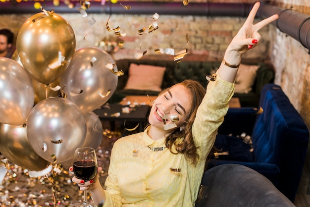 Uśmiechnięta kobieta w partyjnego mienia wina szkle cieszy się w przyjęciu