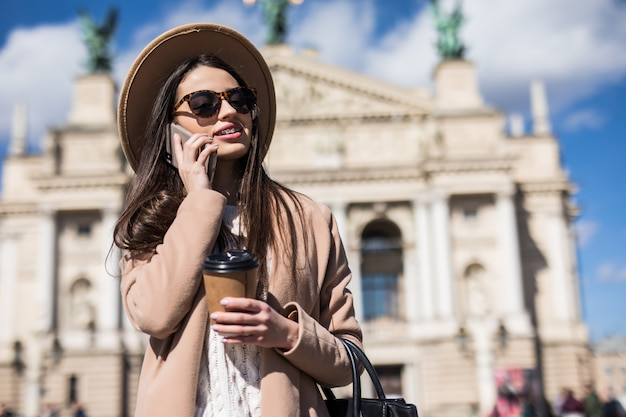 Uśmiechnięta kobieta w przypadkowych ubraniach jesiennych rozmawia przez telefon