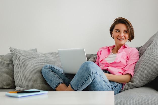 Uśmiechnięta kobieta w różowej koszuli siedzi zrelaksowany na kanapie w domu przy stole, pracując online na laptopie z domu