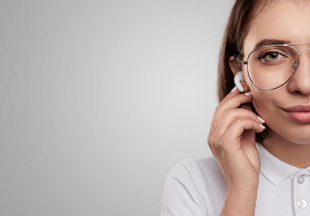 Uśmiechnięta kobieta w słuchawkach patrząc na kamery w studio