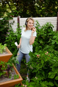 Uśmiechnięta kobieta w słuchawkach pracuje z kwiatami w ogrodzie