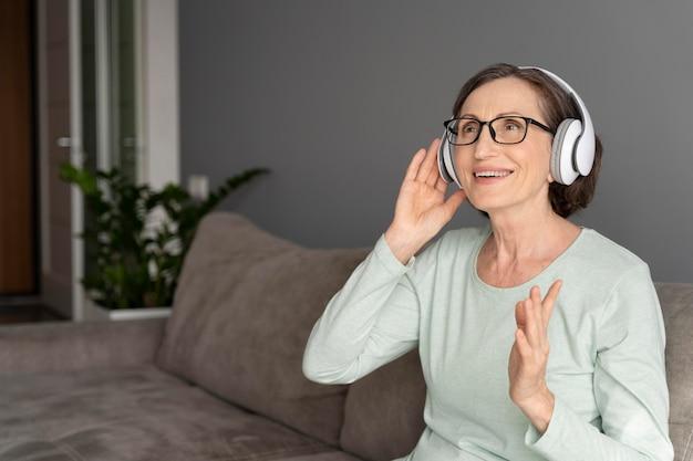 Uśmiechnięta kobieta w słuchawkach średni strzał