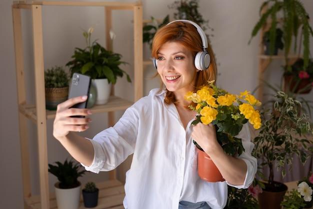Uśmiechnięta kobieta w średnim ujęciu biorąca selfie