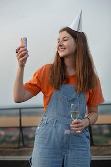 Uśmiechnięta kobieta w średnim ujęciu robi zdjęcia