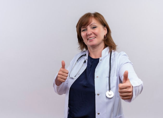 Uśmiechnięta kobieta w średnim wieku lekarz ubrana w szlafrok medyczny i stetoskop pokazujący kciuki do góry na odosobnionej białej ścianie z miejsca na kopię