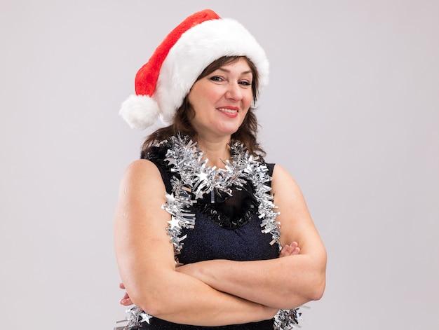 Uśmiechnięta kobieta w średnim wieku nosząca santa hat i blichtrową girlandę wokół szyi stojącej z zamkniętą postawą patrzącą na kamerę odizolowaną na białym tle z kopią przestrzeni