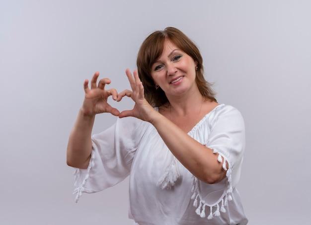 Uśmiechnięta kobieta w średnim wieku pokazująca znak serca z rękami na odosobnionej białej ścianie