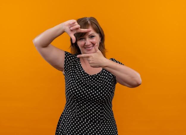 Uśmiechnięta kobieta w średnim wieku robi gest fotografowania na odizolowanych pomarańczowej ścianie z miejsca na kopię