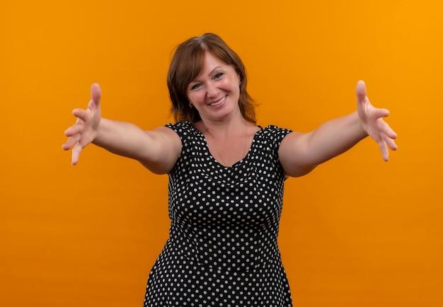 Uśmiechnięta kobieta w średnim wieku, rozciąganie rąk na odosobnionej pomarańczowej ścianie