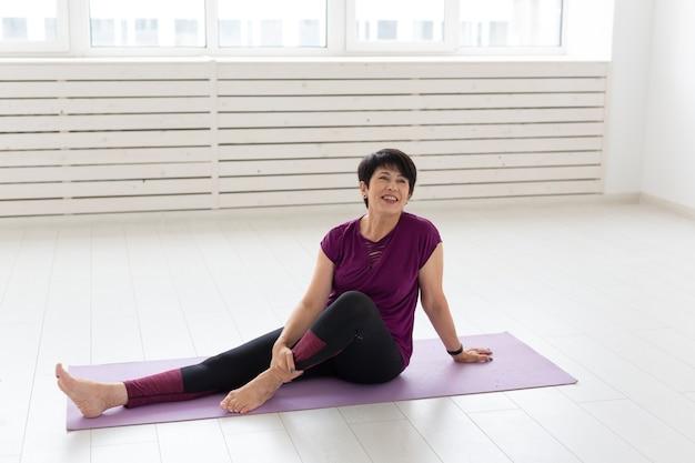 Uśmiechnięta kobieta w średnim wieku siedząca na macie do ćwiczeń