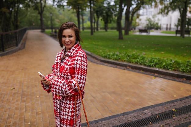 Uśmiechnięta kobieta w średnim wieku, ubrana w jesienne ubrania.