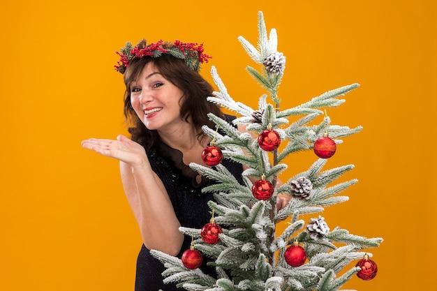 Uśmiechnięta kobieta w średnim wieku ubrana w świąteczny wieniec na głowę i świecącą girlandę wokół szyi stojąca za ozdobioną choinką pokazująca pustą dłoń odizolowaną na pomarańczowej ścianie