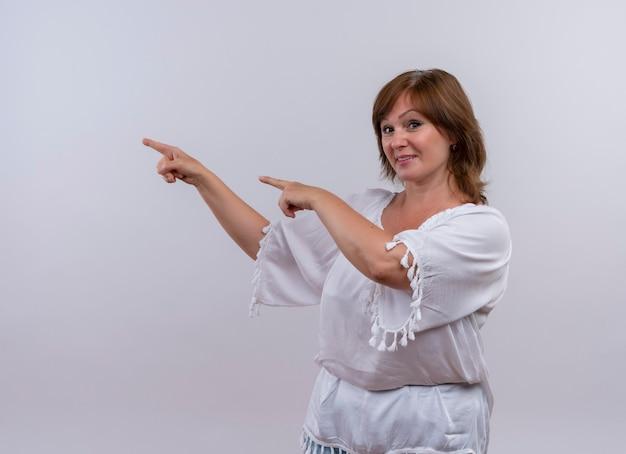 Uśmiechnięta kobieta w średnim wieku, wskazując rękami po lewej stronie i patrząc na odizolowaną białą ścianę