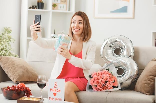 Uśmiechnięta kobieta w szczęśliwy dzień kobiet trzyma prezent i robi selfie siedząc na kanapie w salonie