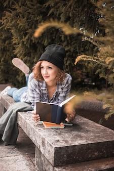 Uśmiechnięta kobieta w szkockiej kraty koszula na kamiennej ławce