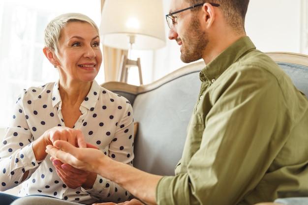 Uśmiechnięta kobieta w wieku kaukaskim, profesjonalna, czytająca dłonie, patrząca na przystojnego, krótkowłosego, młodego męskiego klienta