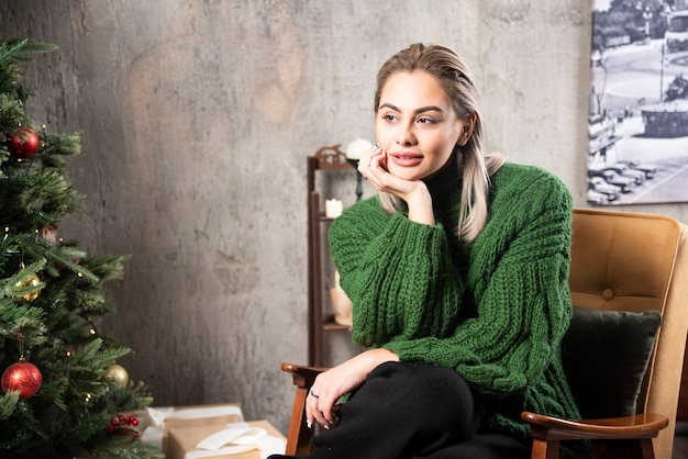 Uśmiechnięta kobieta w zielonym ciepłym swetrze siedzi na krześle i pozowanie