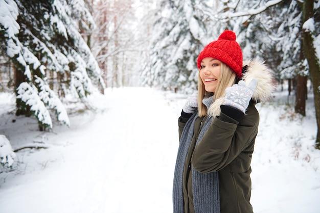 Uśmiechnięta kobieta w zimowym lesie