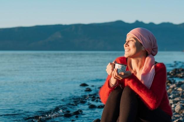 Uśmiechnięta kobieta walcząca z rakiem popija filiżankę herbaty, obserwując zachód słońca nad brzegiem jeziora