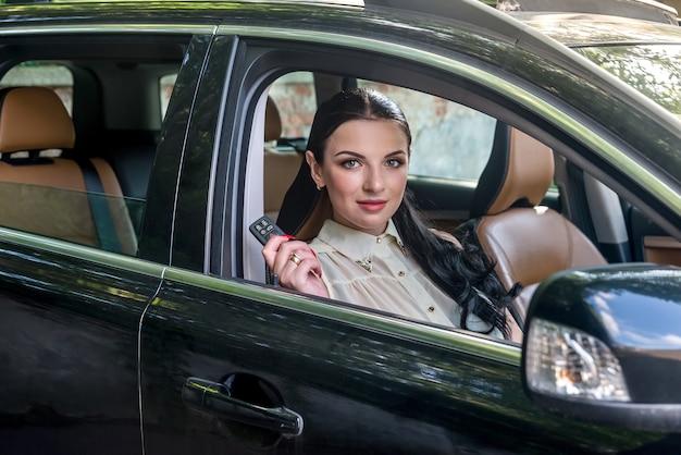 Uśmiechnięta kobieta wewnątrz samochodu z kluczem od niego