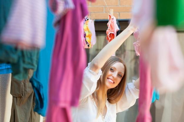Uśmiechnięta kobieta wiszące ubrania po praniu