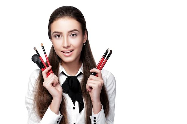 Uśmiechnięta kobieta wizażystka z naturalnym makijażem trzymająca pędzel do makijażu na białym tle