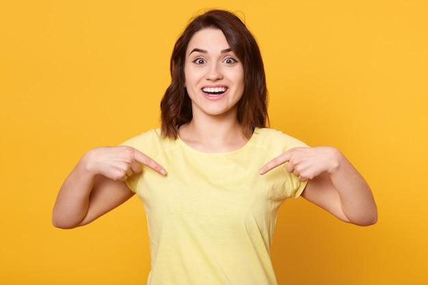 Uśmiechnięta kobieta wskazuje palce na siebie, mając zadowolony i podekscytowany wyraz twarzy