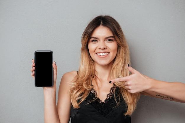 Uśmiechnięta kobieta wskazuje palec przy pustego ekranu telefonem komórkowym