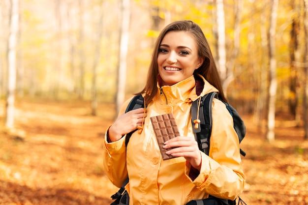 Uśmiechnięta kobieta wycieczkowicz z ciemną czekoladą