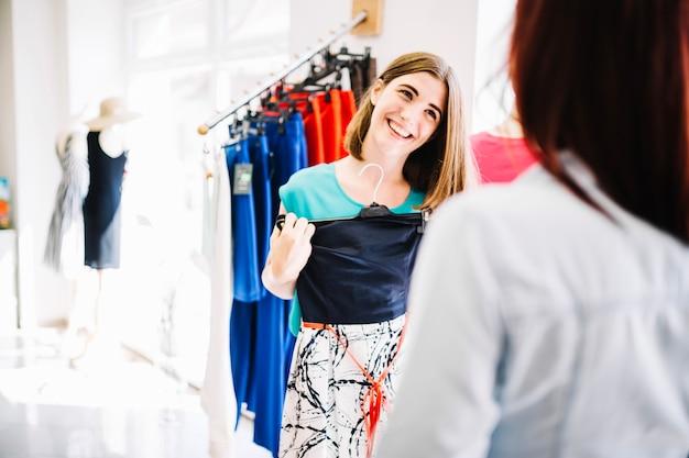 Uśmiechnięta kobieta wykazujące nową sukienkę