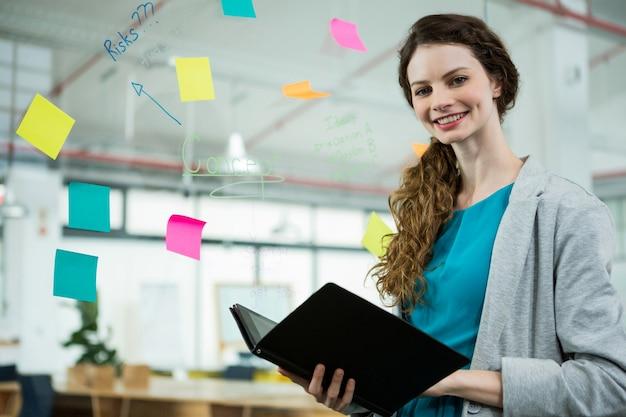 Uśmiechnięta kobieta wykonawcza pozycja z folderem w kreatywnym biurze