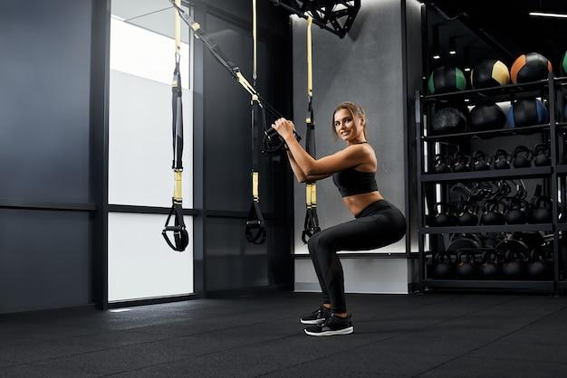 Uśmiechnięta kobieta wykonująca specjalne ćwiczenia z systemem trx