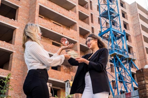 Uśmiechnięta kobieta wynajmuje nowy dom, przekazując pieniądze pośrednikowi. koncepcja sprzedaży