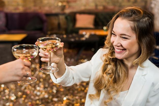 Uśmiechnięta kobieta wznosi toast whisky z jej przyjacielem w przyjęciu