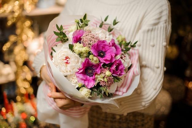 Uśmiechnięta kobieta z bukietem delikatnych kwiatów w kolorze różowym i fioletowym