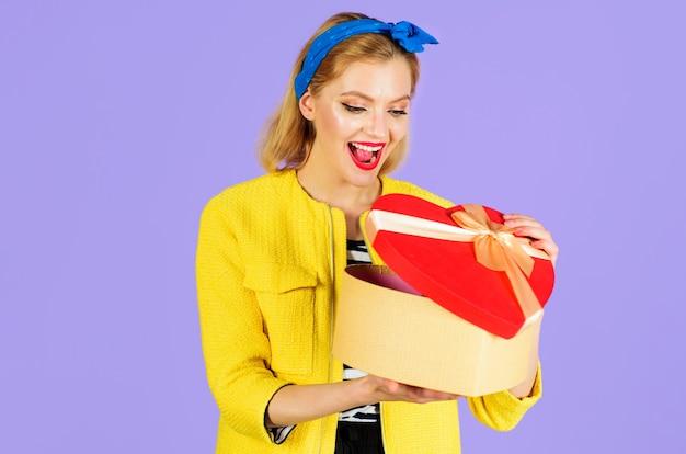 Uśmiechnięta kobieta z czerwonym pudełkiem w kształcie serca