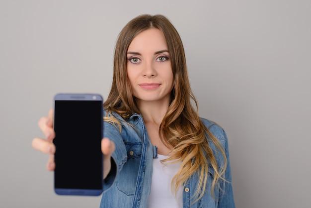 Uśmiechnięta kobieta z długimi brązowymi włosami i dżinsami koszulowymi pokazuje pusty czarny ekran jej smartfona; na białym tle na szarym tle