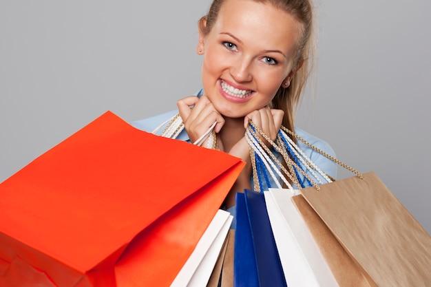 Uśmiechnięta kobieta z dużą ilością toreb na zakupy
