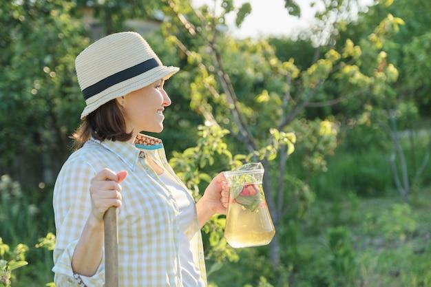 Uśmiechnięta kobieta z dzbankiem odświeżający naturalny domowej roboty napój
