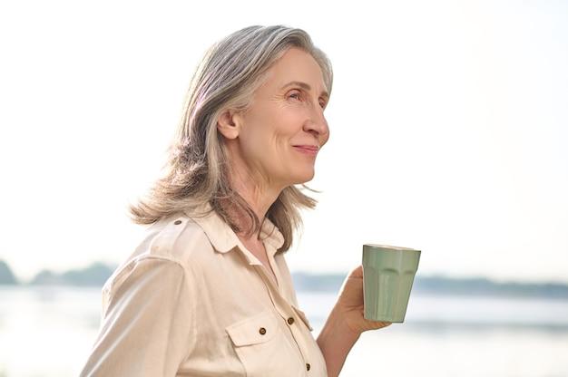 Uśmiechnięta kobieta z filiżanką kawy w naturze