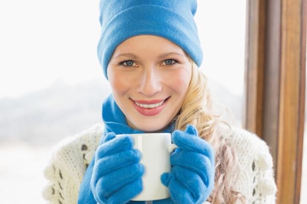 Uśmiechnięta kobieta z filiżanką w ciepłej odzieży przeciw okno