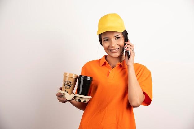 Uśmiechnięta kobieta z filiżankami rozmawiająca przez telefon