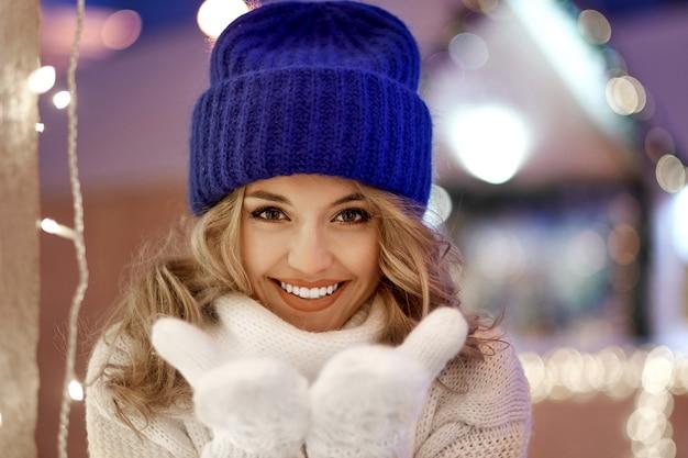 Uśmiechnięta kobieta z girlandami i wakacyjnymi światłami na świątecznych jarmarkach bożych narodzeń lub nowego roku.