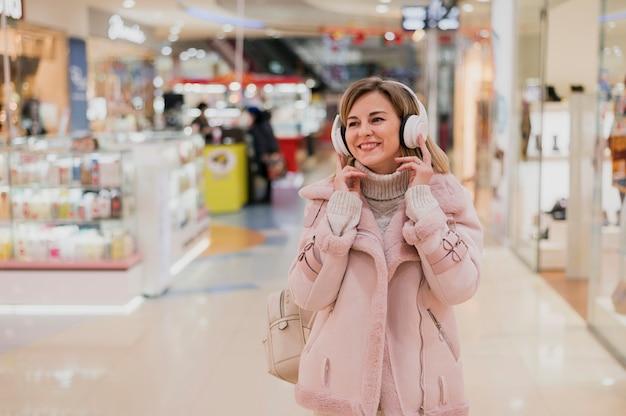 Uśmiechnięta kobieta z heaphones w zakupy centrum handlowym