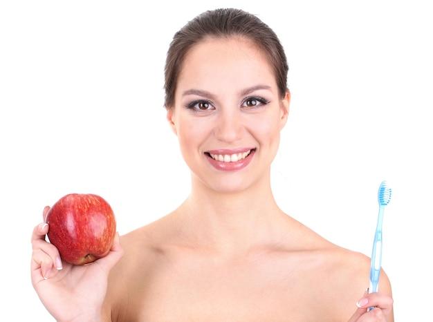 Uśmiechnięta kobieta z jabłkiem i szczoteczką do zębów na białym tle