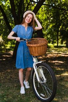 Uśmiechnięta kobieta z jej rowerem
