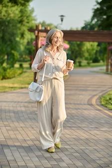 Uśmiechnięta kobieta z kawą spacerująca w parku
